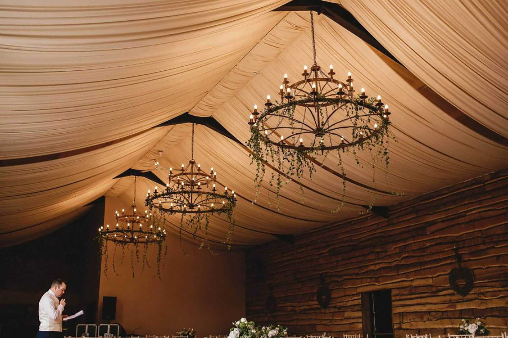 "Our enormous chandeliers in the wedding barn. Photo by <a href=""https://andygaines.com/"" target=""_blank"">Andy Gaines</a>."