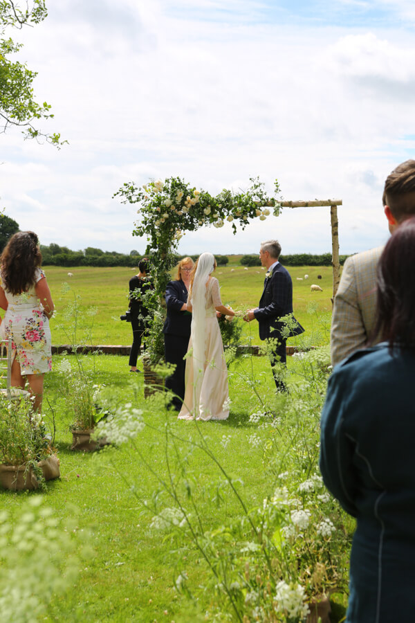 Katie and Andrew saying their vows under a flower-adornded archway on the Manor Lawn. Photography by Simon Stock.