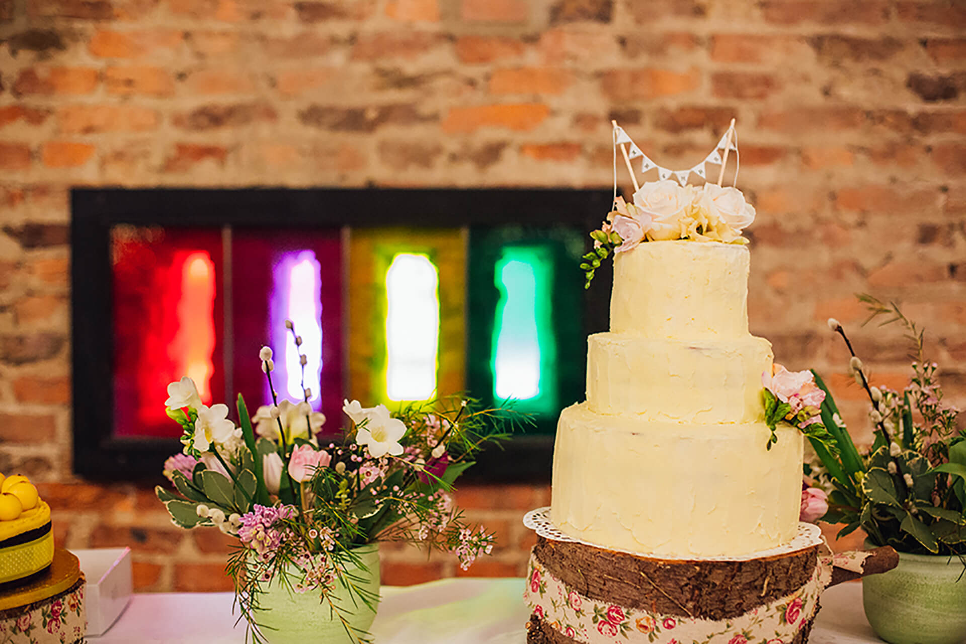 "Sophie and Stevens cake looks amazing against our colorful barn window backdrop! Photo by <a href=""http://www.cjrodgersphotography.co.uk/"" target=""_blank"">CJ Rodgers</a"