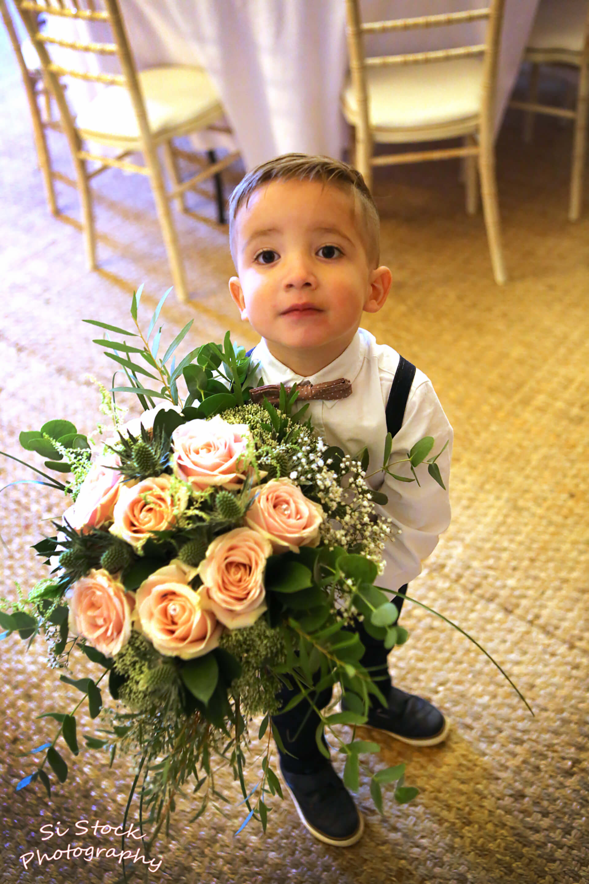 Beautiful roses and the most adorable page boy at Joe and Rachel's wedding. Photo by Simon Stock.